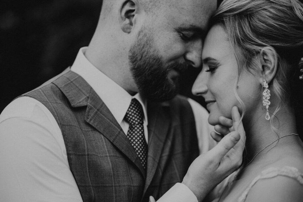 czarno białe zdjęcie ślubne z pleneru w sukni i kamizelce pana młodego