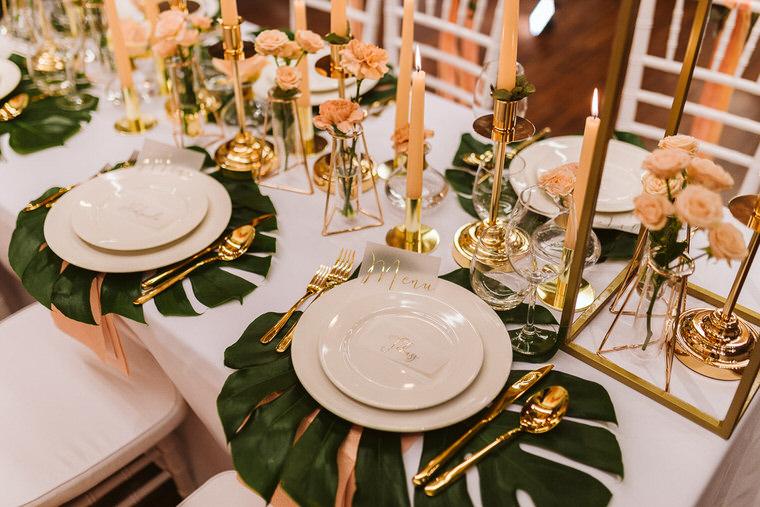 dekoracje na wesele living coral blady róż świece złote sztućce kwiaty na stół liście monstera